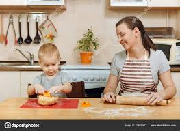 little kid boy helps mother to cook christmas ginger biscuit in