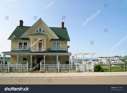 yellow victorianstyle house green roof blue stock photo 1734944
