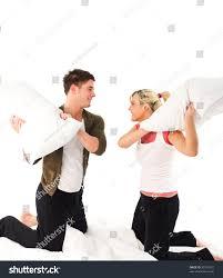 happy boyfriend girlfriend having pillow fight stock photo