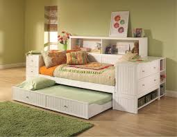unstained wooden pop up trundle bed with white bed linen and