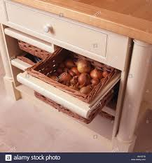kitchen storage units close up of onions stored in basket in fitted kitchen storage unit