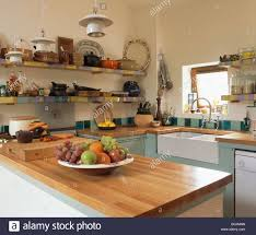 cherry wood worktop in small country kitchen with belfast sink and