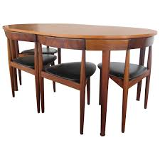 rare hans olsen teak table with leaf and six chairs that tuck
