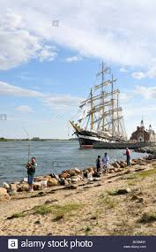 people fishing along cape cod canal with tall ship kruzenshtern