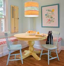 small yet comfy dining room with yellow round dining table corner sofa blue wooden chairs and pendant lamp with blue wall color image