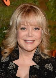 candy spelling medium blonde curly hairstyle with bangs for women