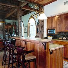 modern kitchen area with dark cabinets wrap around natural stone