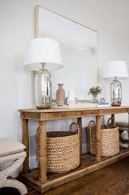 light wood console table beige x stools flank a reclaimed wood console table fitted with a