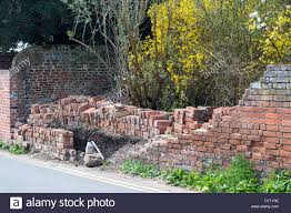 the remains of an old brick garden wall after it had collapsed