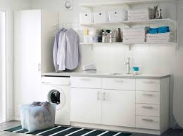 a laundry room with white wall shelves base cabinets with doors or drawers and a