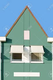 a dutch house with a triangular gable roof gutters and sunscreen