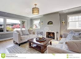 light grey living room with white sofas and fireplace stock photo