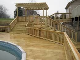 brown wooden deck with wooden railing plus brown wooden pergola