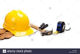 a yellow hard hat leather work gloves and various construction
