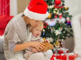 young mom and baby playing near christmas tree stock photo