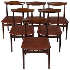 set of six rosewood and black leather dining chairs by christian