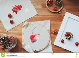 christmas cross stitch designs and decorations on wooden table