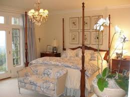 floral sofa and wooden four poster bed for classic master bedroom