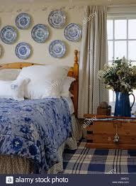 collection of blue and white china plates on wall above bed with
