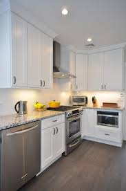 travertine countertops white shaker kitchen cabinets lighting