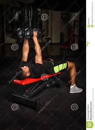 young man doing arms bench flies workout in gym stock photo