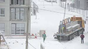 snow falling and construction site workers build house in dramatic