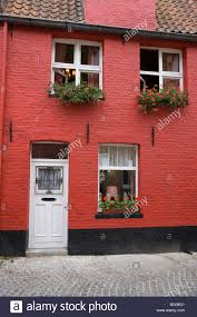 pretty red painted brick house with window boxes full of flowers