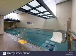 indoor swimming pool entry ladder and disabled person chair stock