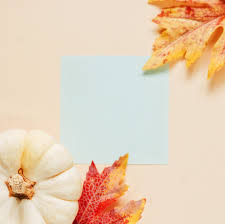 flat lay of minimal workspace blank notebook with autumn leaves