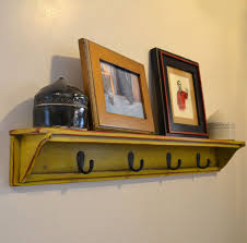 rustic yellow stained wooden wall coat rack with black iron hooks