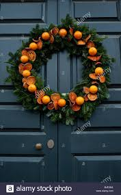 an orange christmas wreath decorating a door at colonial