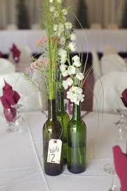 Non Flower Centerpieces For Wedding Tables by Wine Bottles Wrapped In Lace With Branches Sticking Out For Rustic