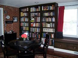 mocha stained wooden corner bookshelf attached on exposed brick