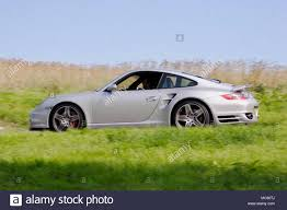 porsche side view low angle profile side view of a silver porsche 911 997 driving