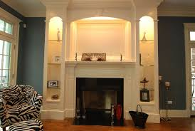 large white wooden shelving around black fireplace with mantels