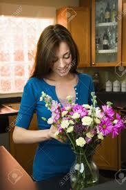 Arranging Roses In Vase Pretty Caucasian Young Woman Arranging Flowers In Vase In Kitchen