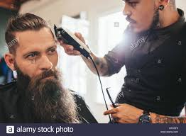 young man getting haircut at barber shop hairstylist cutting hair