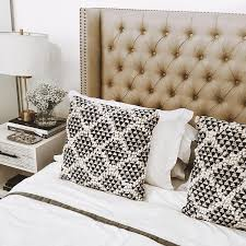 taupe tufted wingback headboard with black and white pillows