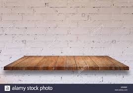top of wooden shelf with white brick wall decorated in coffee shop