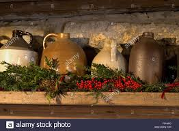 crock jugs on mantel with christmas decorations and berries inside