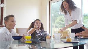 mother offering cookies to her family at home in kitchen stock