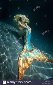 mermaid sitting on the ground underwater stock photo royalty free