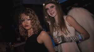 group of young girls in halloween costumes dancing with drinks