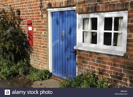 blue front door and old post box set in brick wall of cottage in
