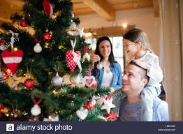 At Home Christmas Trees by Young Family With Daugter At Christmas Tree At Home Stock Photo