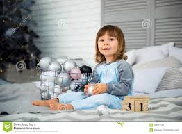 small cute little is 2 years old sitting near christmas tree