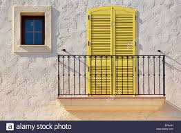 white house facade with a balcony a yellow balcony door and a