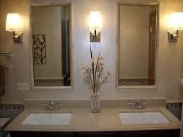 marble top over a custom vanity with tile around the mirrors by