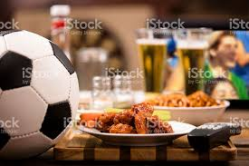 television cuisine soccer on television at local pub chicken wings stock