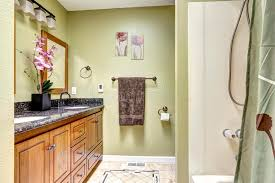 bright bathroom in light green tone wooden cabinet with granite
